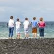 Stock Photo: Family watches the waves at the black volcanic beach