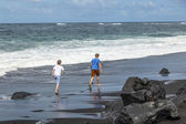 Boys have fun at the black volcanic beach — Stock Photo