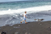 Boy has fun at the black volcanic beach — Stock Photo