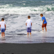 Boys have fun at the black volcanic beach — Stock Photo #10668176