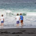 Boys have fun at the black volcanic beach — Stock Photo #10668269