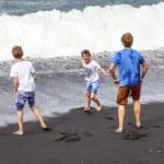 Boys have fun at the black volcanic beach — Stock Photo #10668478