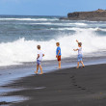 Boys have fun at the black volcanic beach — Stock Photo #10669039