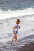 Boy has fun in the spume at the black volcanic beach — Stock Photo