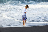 Boy watches the spume of the ocean — Stock Photo