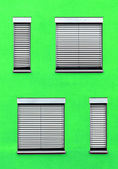 Pattern of windows with green wall — Stock Photo