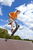Boy jumping over a ramp with his scooter — Stock Photo