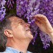Stock Photo: Attractive man is smelling park flowers
