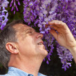 Attractive man is smelling park flowers — Stock Photo