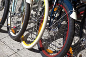 Bicycle wheels lined up — Stock Photo
