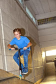 Boy jumping with his scooter over a ramp in the skatehall — Stock Photo