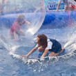 Girls and boys have fun in huge zorbing ball — Stock Photo #8594076