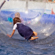 Girls and boys have fun in a huge zorbing ball — Stock Photo