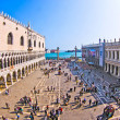 Tourists on San Marco square feed large flock of pigeons - Stock Photo