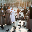 Nons on San Marco square feed large flock of pigeons - Stock Photo