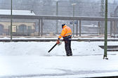 Worker is cleaning the platform of a train station from snow — Stock Photo