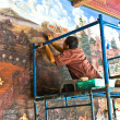 Stock Photo: Worker restores the famous paintings in the Grand Palace precise