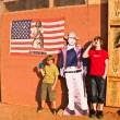 Постер, плакат: Family is posing with a picture of John Wayne at John Fords pla