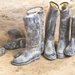 Dirty plastic riding boots standing at the muddy gry ground — Stok fotoğraf