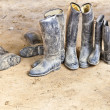 Dirty plastic riding boots standing at the muddy gry ground — Stock Photo