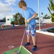 Stockfoto: Boy playing mini golf in the course