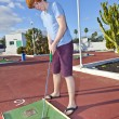 Stock Photo: Boy playing mini golf in the course