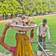 Female worker carries rock waste on her hat - Stock Photo