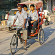 Rickshaw rider transports passenger — Stock Photo #8895073