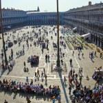 Постер, плакат: Tourists on San Marco square feed large flock of pigeon