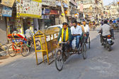 Rickshaw rider transports passenger — Stock Photo