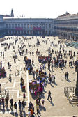 Tourists on San Marco square feed large flock of pigeons — Stock Photo