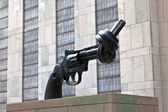 Gun tied in a knot outside UN headquarters as symbol for reachin — Stock Photo