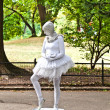 Woman dressed as a ballet dancer in white shows pantomines to co - Stock Photo