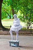 Woman dressed as a ballet dancer in white shows pantomines to co — Stock Photo