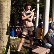 Постер, плакат: Girl made up as Lara Croft and poses for photografers