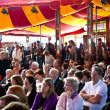 Stock Photo: Spectators are listening authors in reading tent
