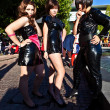 Three girls in black in costumes  are posing for photografers — Stockfoto