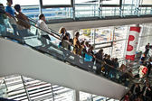 Visitors inside the fair hall on moving staircase — Stock Photo