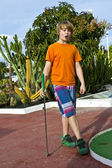 Boy playing mini golf in the course — Stock Photo