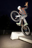 Boy jumping with his bike over a ramp by night — Stock Photo