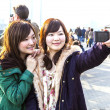 Japanese tourists take self-portraits - Stock Photo