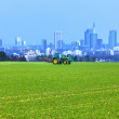 Stock Photo: Tractor on the field with Skyline of Frankfurt