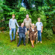 Extended family group posing in the garden with grandparents — Stock Photo
