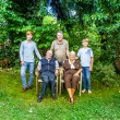 Extended family group posing in the garden with grandparents - Stock Photo