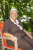 Senior woman enjoys sitting in her — Stock Photo