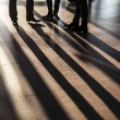 Feet of hurrying in the airport with sown shadows — Stockfoto