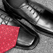 Black leather dress shoes and necktie — Stock Photo