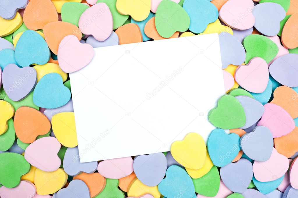 A blank Valentine's card in a pile of heart shaped pastel candies. Blank card is for placement of copy.  Stok fotoraf #9336913