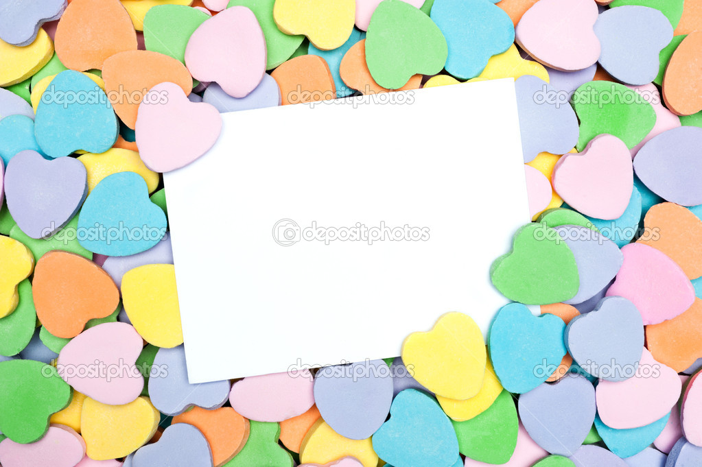 A blank Valentine's card in a pile of heart shaped pastel candies. Blank card is for placement of copy. — Photo #9336913