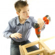 Stock Photo: Child with a screwdriver engaged in assembling furniture